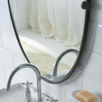 Specchio con cornice in metallo anticato.